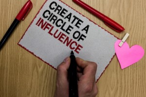 Text sign showing Create A Circle Of Influence. Conceptual photo Be an influencer leader motivate other people Written sticky note clip pinch heart hand hold marker red pen on wooden desk.